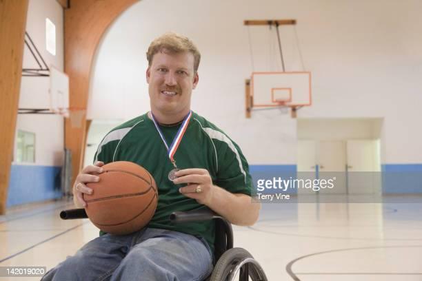 Caucasian man in wheelchair holding basketball medal