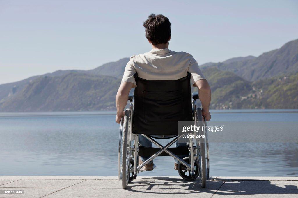 Caucasian man in wheelchair sitting on dock : Stock Photo