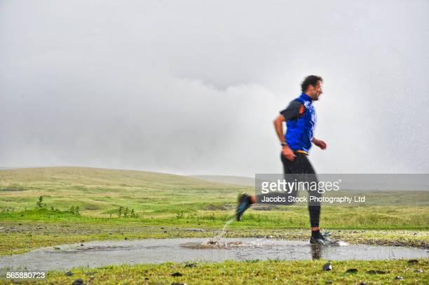 Caucasian man jogging in puddle in rural field
