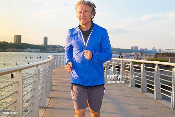 Caucasian man jogging on urban waterfront