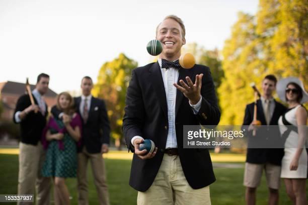 Caucasian man juggling croquet balls