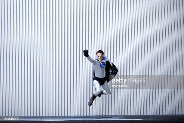 Caucasian man jumping in superhero costume