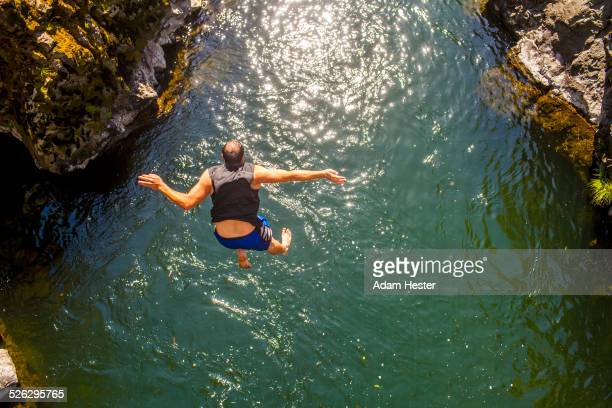 Caucasian man jumping off rocks into ocean