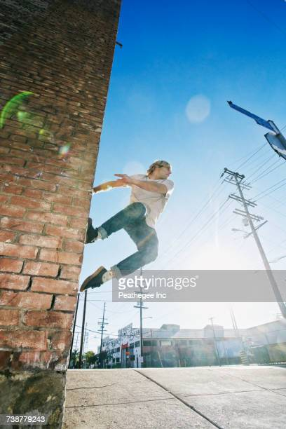 caucasian man jumping on urban wall - le parkour stock-fotos und bilder
