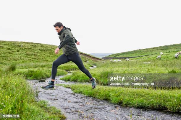 caucasian man jumping over creek in rural field - only mid adult men stock pictures, royalty-free photos & images