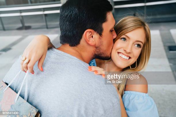 Caucasian man kissing cheek of woman carrying shopping bag