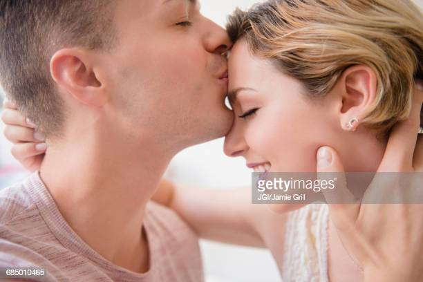 caucasian man kissing girlfriend on forehead - heterosexual couple stock pictures, royalty-free photos & images