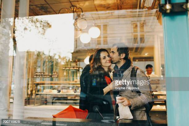 Caucasian man kissing woman on cheek behind bakery window