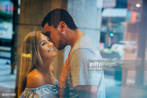 Caucasian man kissing woman on cheek behind window