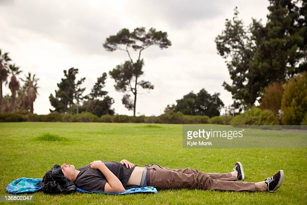 Caucasian man laying in grass in park