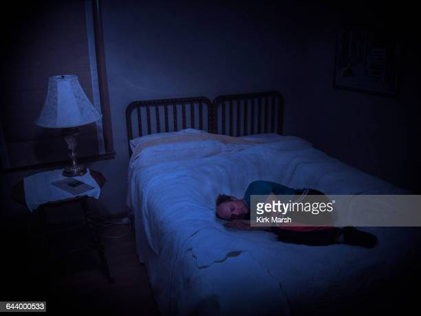 caucasian man laying in sinking bed - fetal position stock photos and pictures