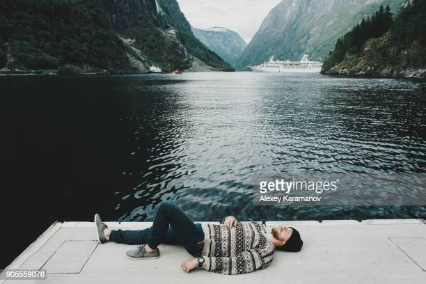 Caucasian man laying on dock at waterfront