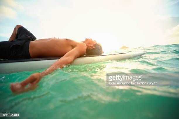 Caucasian man laying on paddle board in ocean