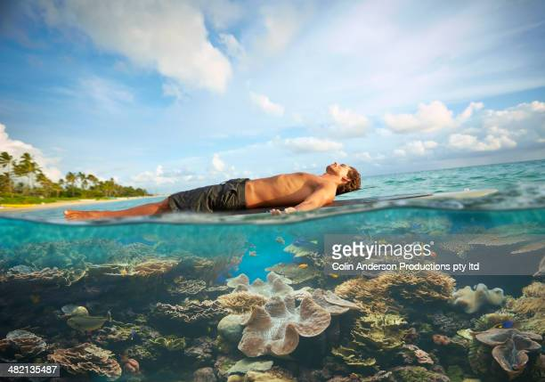 Caucasian man laying on paddle board in tropical ocean
