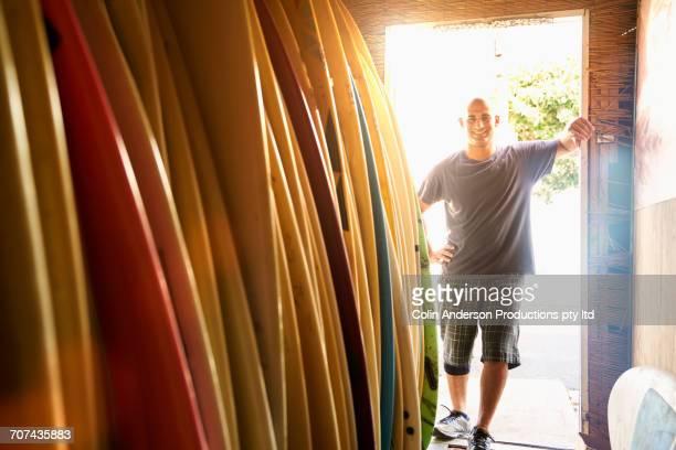 Caucasian man leaning in doorway of surfboard shop