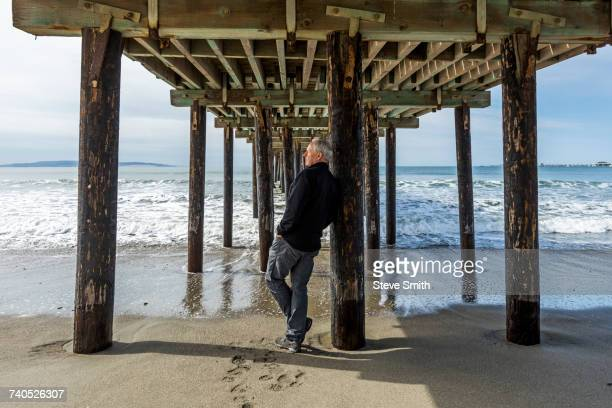 Caucasian man leaning on piling of wooden pier at beach