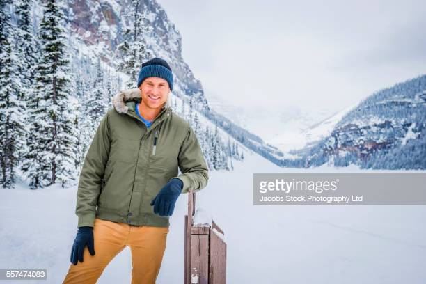 Caucasian man leaning on post near snowy mountains, Lake Louise, Alberta, Canada