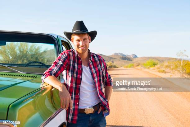 caucasian man leaning on truck on rural road - cowboy hat stock pictures, royalty-free photos & images