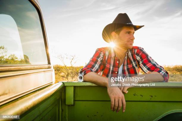 Caucasian man leaning on truck outdoors