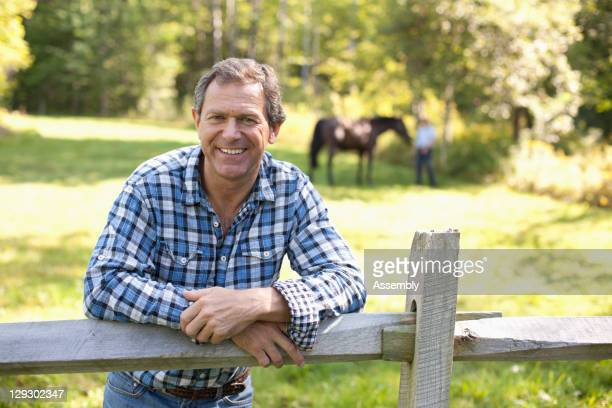 caucasian man leaning on wooden fence - incidental people stock pictures, royalty-free photos & images