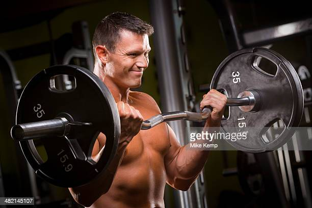 Caucasian man lifting barbell in gym