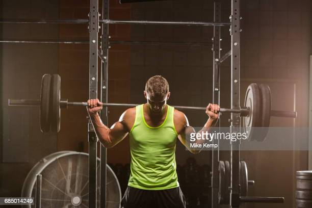 Caucasian man lifting barbell in gymnasium