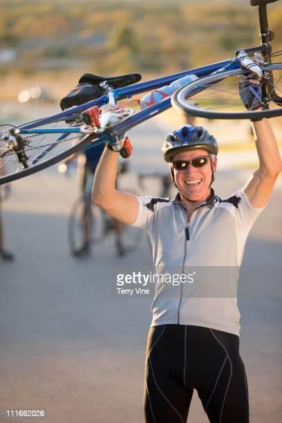 Caucasian man lifting bicycle