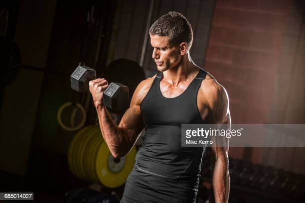 Caucasian man lifting dumbbell in gymnasium