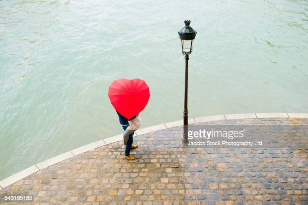 Caucasian man lifting girlfriend under heart shape umbrella