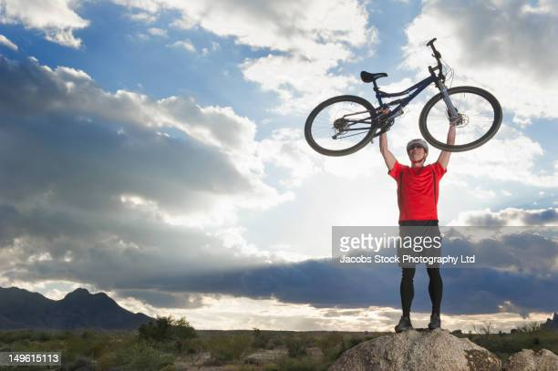 Caucasian man lifting mountain bike in remote area