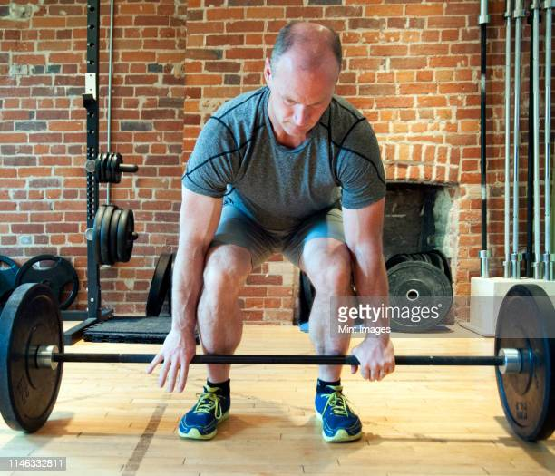 caucasian man lifting weights in gymnasium - receding hairline stock pictures, royalty-free photos & images