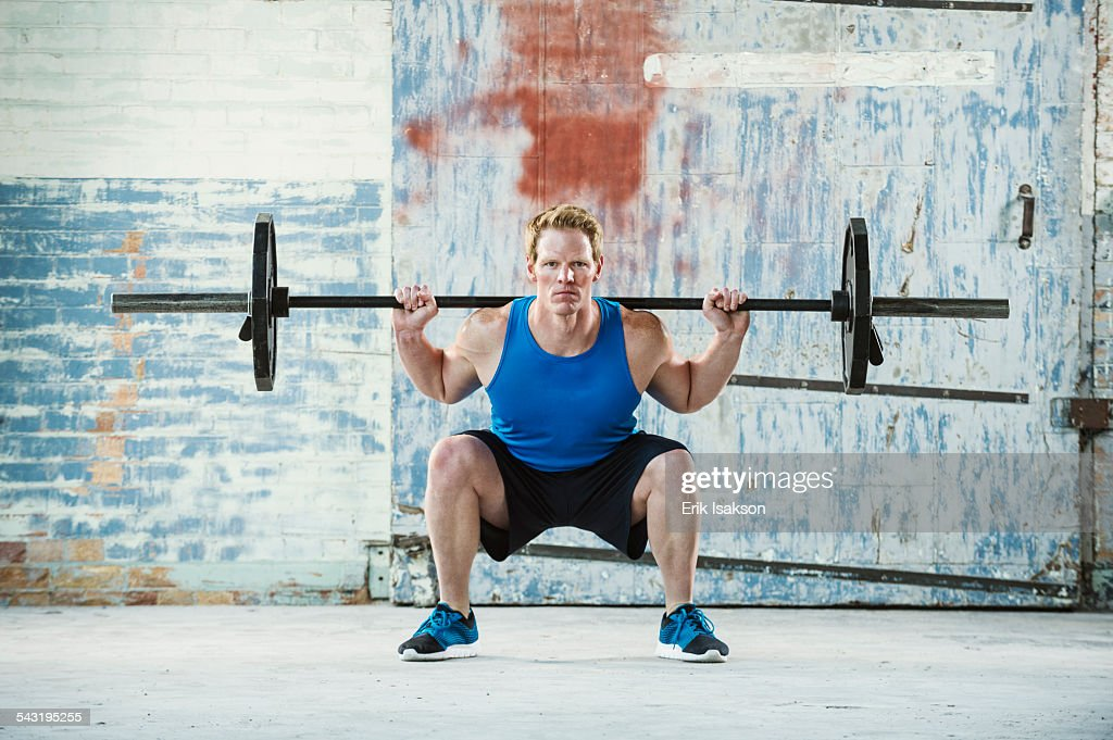 Caucasian man lifting weights in warehouse : Stock Photo