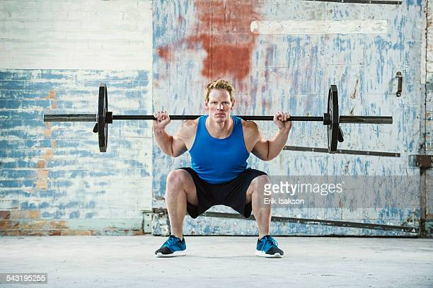caucasian man lifting weights in warehouse - hurken stockfoto's en -beelden