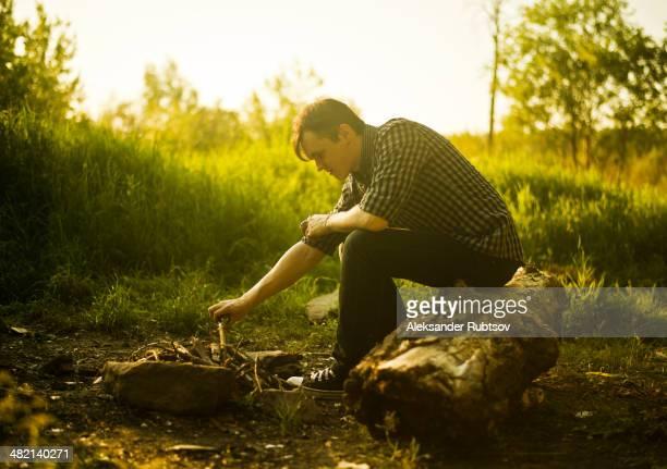 Caucasian man lighting campfire in rural field