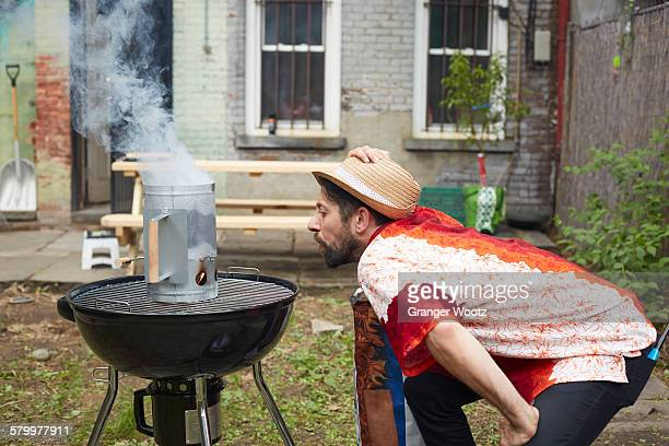 caucasian man lighting charcoal for grill in backyard - stoking stock pictures, royalty-free photos & images