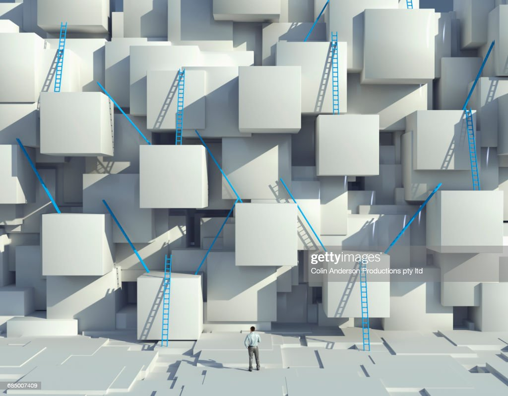 Caucasian man looking at blue ladders on cube wall : Stock Photo