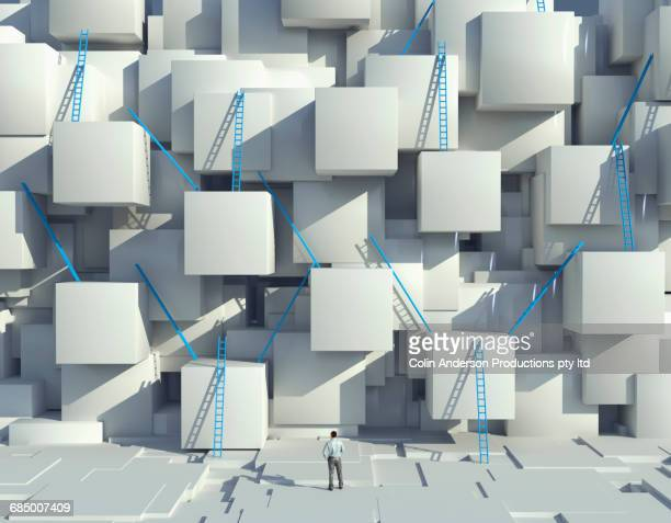 Caucasian man looking at blue ladders on cube wall