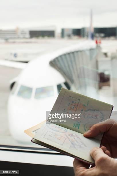 Caucasian man looking at passport in airport