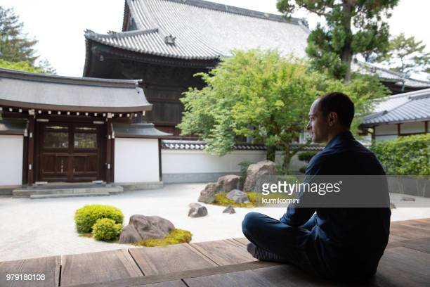 caucasian man looking at temple garden - cross legged stock pictures, royalty-free photos & images
