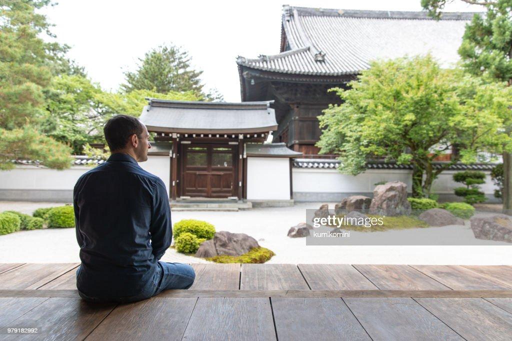 Caucasian man looking at temple garden : Stock Photo