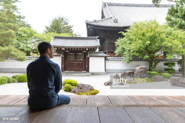 caucasian man looking at temple garden - japanese garden stock photos and pictures