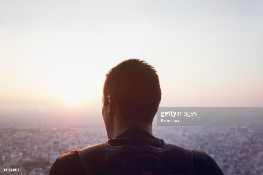 Caucasian man looking down the cityscape of Tokyo : Stock-Foto