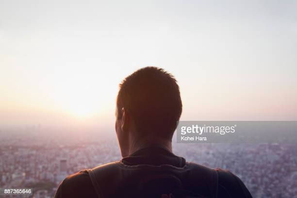 Caucasian man looking down the cityscape of Tokyo