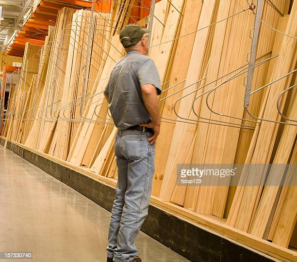 Caucasian man looking, shopping for lumber in a Hardware store