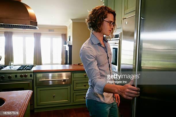Caucasian man looking through fridge