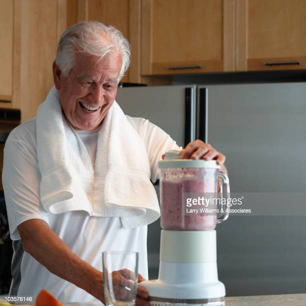Caucasian man making smoothie in kitchen