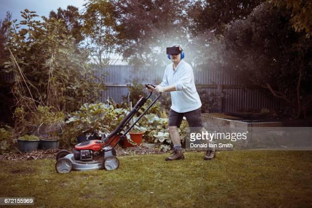 caucasian man mowing lawn with vr goggles - jardinier humour photos et images de collection