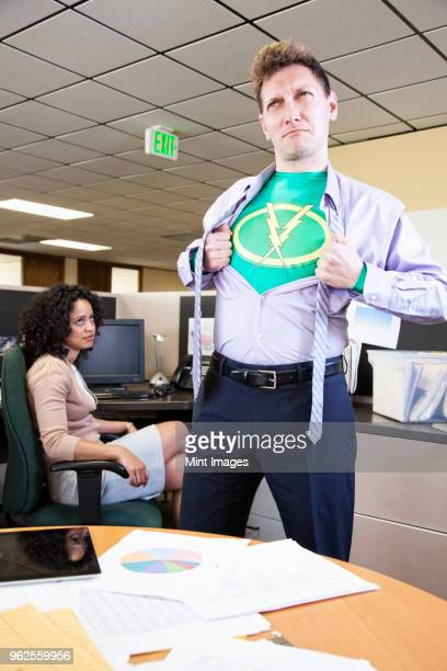 a caucasian man office super hero gets ready for action in his office. - superman stock pictures, royalty-free photos & images