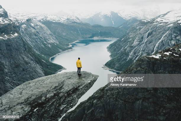 caucasian man on cliff admiring scenic view of mountain river - norwegen stock-fotos und bilder