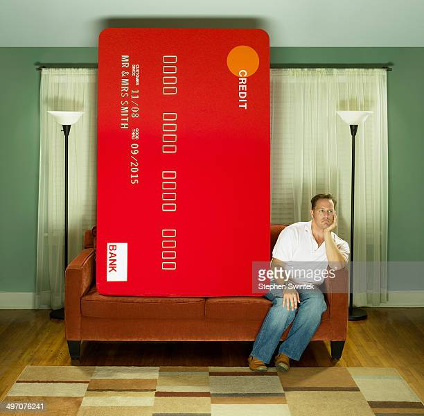 caucasian man on couch with oversized credit card